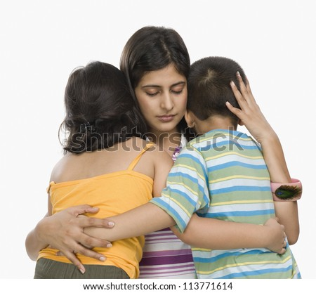 Close-up of a mother hugging her children - stock photo