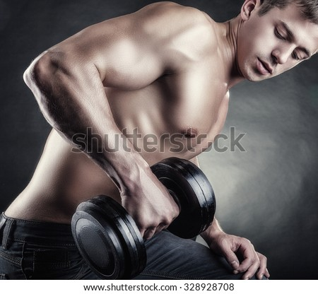 Close-up of a muscular young man lifting weights on dark background. Focus on hand - stock photo