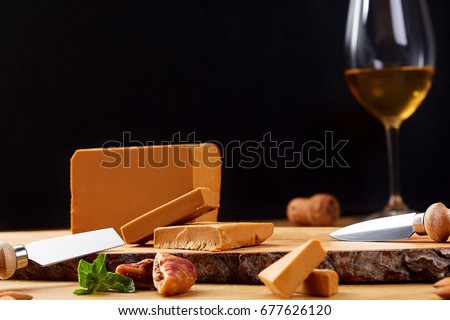 Close-up of a norwegian Gudbrandsdalen cheese with glass of wine. Cheese on wooden board.