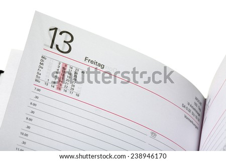 Close up of a open diary - 13 friday (german - Freitag), isolated on white background