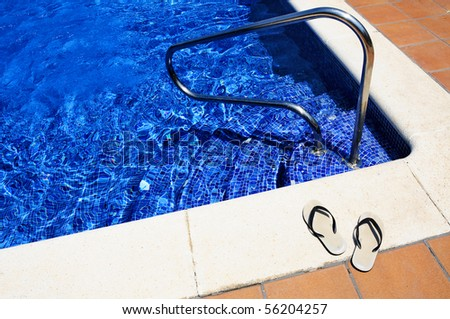 close up of a pair of flip-flops on a swimming pool in the summer - stock photo