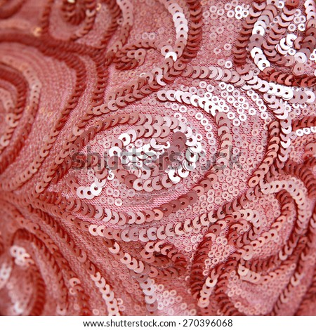 Close up of a pale pink dress covered with shiny pink sequins  - stock photo