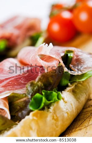 Close up of a parma ham sandwich with tomatoes in the background - stock photo