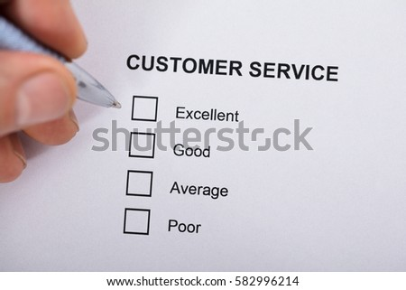 Close-up Of A Person Filling Customer Service Satisfaction Survey Form On Wooden Desk