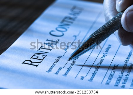 Close-up Of A Person  Filling Rental Agreement Form With Pen - stock photo