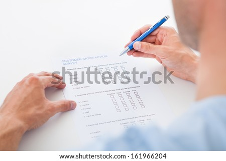 Close-up Of A Person Filling Survey Form With Pen - stock photo