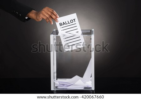 Close-up Of A Person Hand Inserting Ballot In Glass Box Against Gray Background - stock photo
