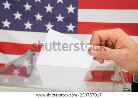 Close-up Of A Person In Front American Flag Putting Ballot In Glass Box