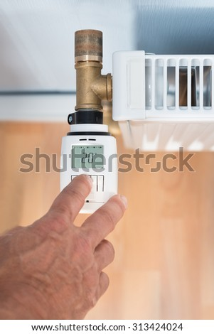 Close-up Of A Person's Hand Adjusting Temperature On Thermostat - stock photo