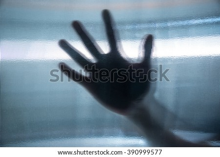 Close-up of a person's hand behind glass.