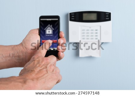 Close-up Of A Person's Hand Disarming System With Remote Control. Photographer owns copyright for images on screen - stock photo