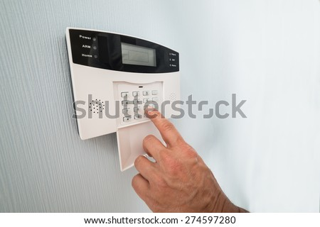 Close-up Of A Person's Hand Entering Code In Security System - stock photo