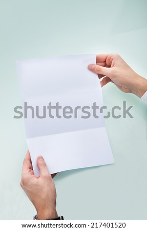 Close-up Of A Person's Hand Holding Blank Paper - stock photo