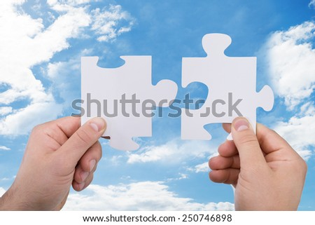 Close-up Of A Person's Hand Holding Jigsaw Pieces Against Sky - stock photo