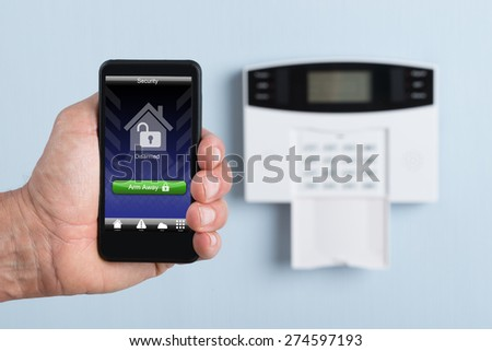 Close-up Of A Person's Hand Holding Remote Control Of Security System. Photographer owns copyright for images on screen