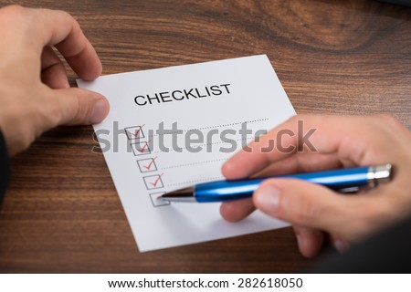 Close-up Of A Person's Hand Marking On Checklist With Pen - stock photo