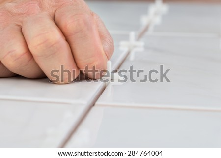 Close-up Of A Person's Hand Placing Spacers Between Ceramic Floor Tiles - stock photo