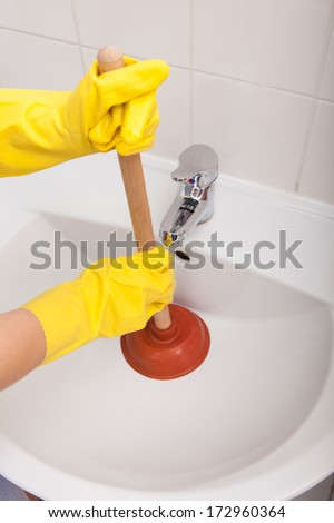 Close-up Of A Person's Hand Pressing Plunger In Sink - stock photo
