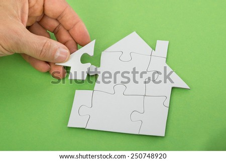 Close-up Of A Person's Hand Solving House Jigsaw Puzzle - stock photo