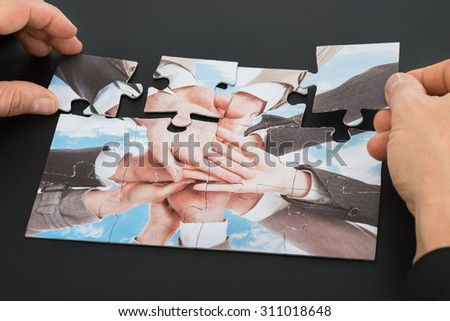 Close-up Of A Person's Hand Solving Jigsaw Puzzle - stock photo