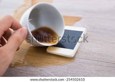 Close-up Of A Person's Hand Spilling Coffee On Cellphone - stock photo