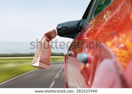 Close-up Of A Person's Hand Throwing Trash Out Of Car Window - stock photo