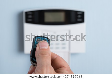 Close-up Of A Person's Hand Using Remote Control To Disarm The Security System - stock photo