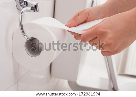 Close-up Of A Person's Hand Using Toilet Paper - stock photo