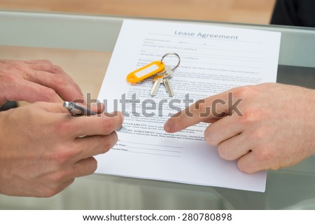 Close-up Of A Person Signing Lease Agreement - stock photo