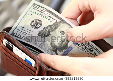 Close-up of a person taking banknotes from wallet. - stock photo