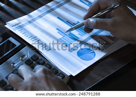 Close-up Of A Person Using Calculator And Analyzing Graph - stock photo