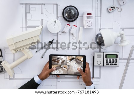 Closeup person watching footage on digital stock photo 767181493 close up of a person watching footage on digital tablet with security equipments on blueprint malvernweather Images