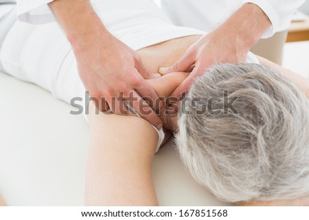 Close-up of a physiotherapist massaging a senior woman's back in the medical office - stock photo