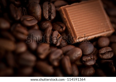 Close up of a piece of chocolate and coffee seeds together