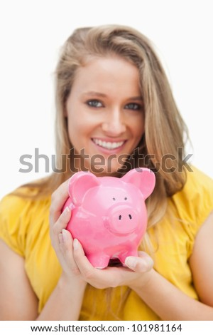 Close-up of a piggy-bank holding by a blond woman against white background