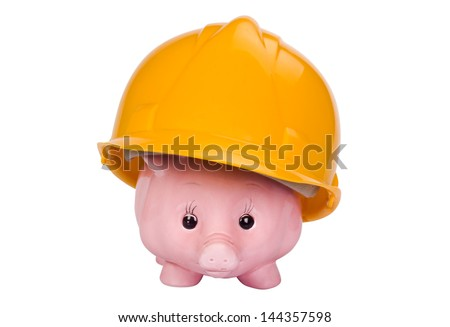 Close-up of a piggy bank with a hardhat - stock photo