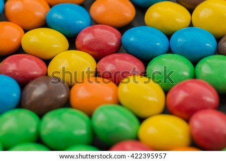 Close up of a pile of colorful chocolate coated candy. Selective focus on background.