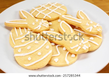 Close up of a pile of iced Easter themed biscuits on a plate - rabbit and egg designs - stock photo