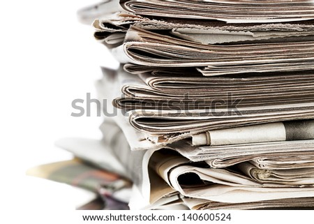 Close-up of a pile of old newspaper displayed on white background. - stock photo