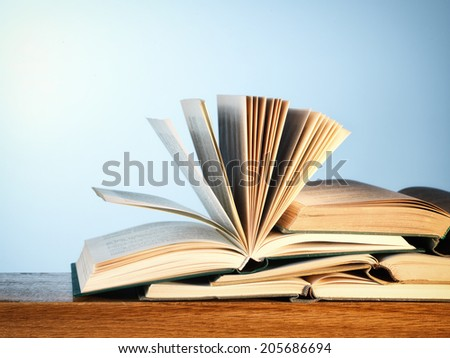 Close-up of a pile of old open novel books on a wooden table, with copy space on blue - stock photo