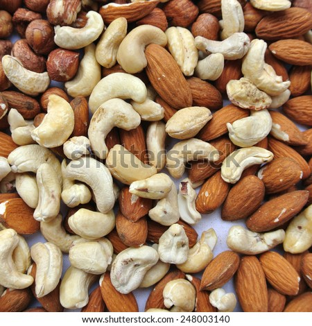 Close-up of a pile of various nuts - almonds, cashews and hazelnuts.   - stock photo