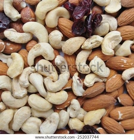Close-up of a pile of various nuts - almonds, cashews and hazelnuts, and dried cranberries.  Healthy/clean eating concept. - stock photo
