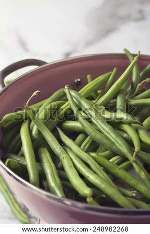 Close up of a pink colander with washed raw green beans - stock photo