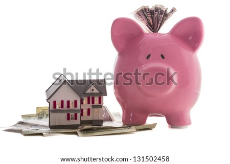 Close up of a pink piggy bank with dollars beside miniature house model on white background - stock photo