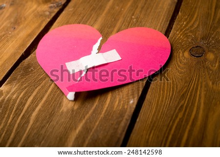 close up of a plaster and paper broken heart on wooden background