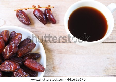 Close up of a plate of dried dates and tea cup on a wooden background. Selective focus.