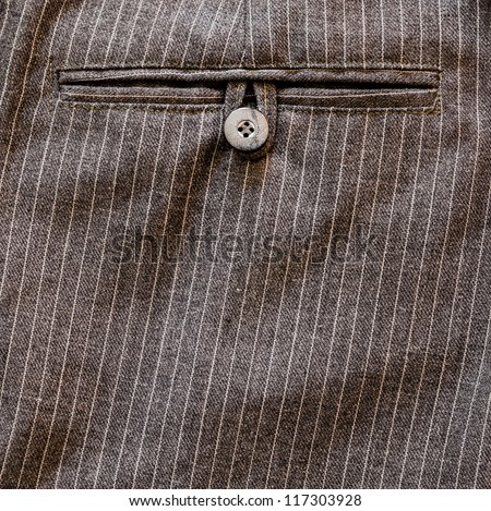 Close up of a pocket button on back of a stripped business suit Pant or trouser. HIgh Contrast. - stock photo