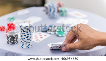 Close-up of a poker player holding playing cards - stock photo