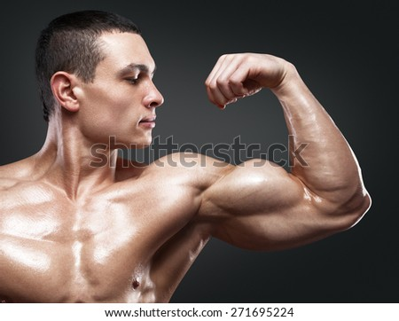 Close-up of a power fitness man's hand. Strong and handsome young bodybuilder demonstrate his muscles and biceps - stock photo