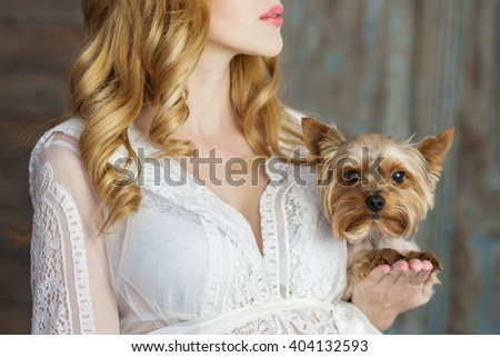 close-up of a pregnant woman in a bright dress is standing and holding hands on the animal small dog